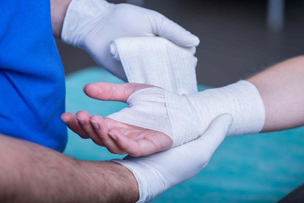 Een hand dat wordt verbonden na een bedrijfsongeval