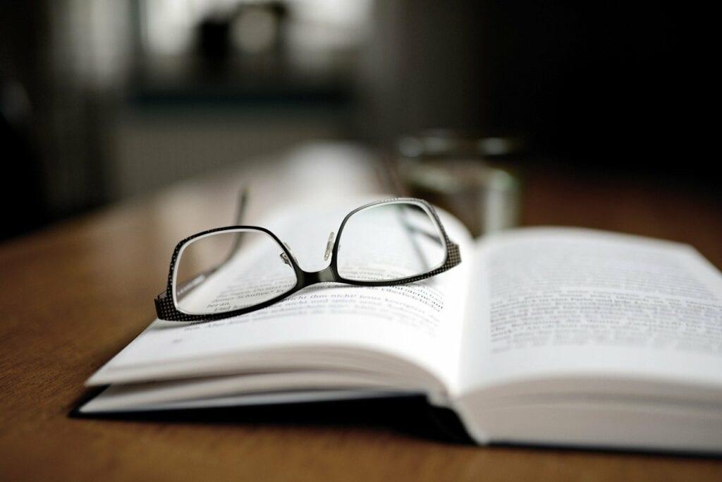 Een bril liggend op een VCA boek