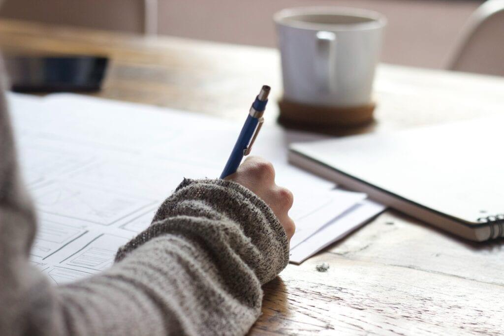Een pen in de hand van iemand die aan het studeren is